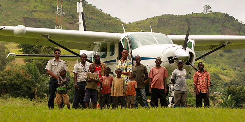 Group of children and men in front of plane mountains in background