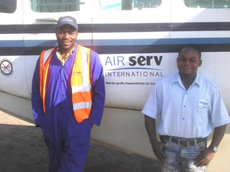 Congolese dedicated employees posing for picture by Air Serv plane