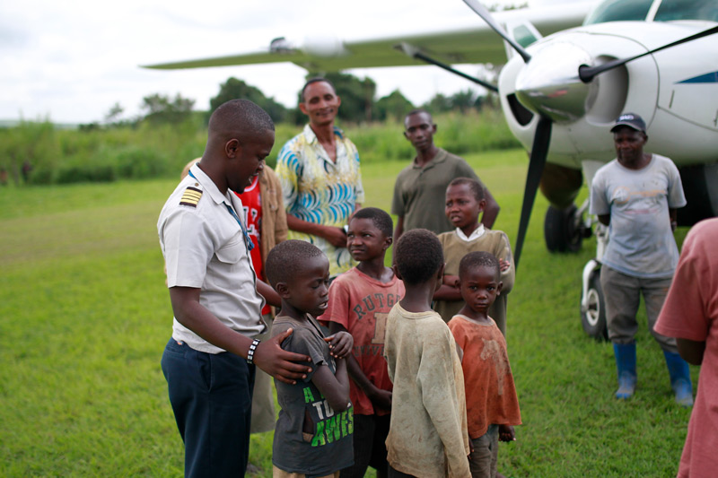 Group of men and children gathered by plane